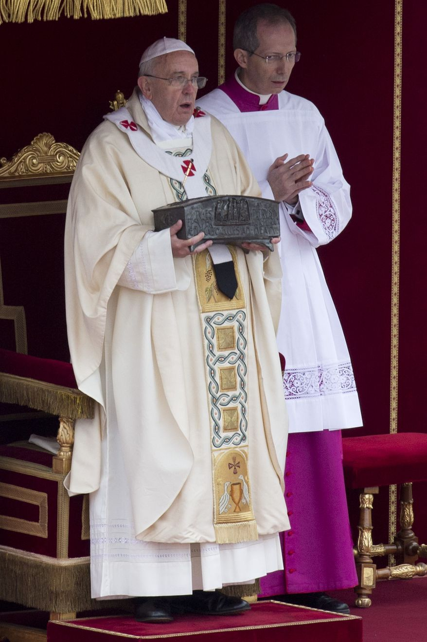 Pope Francis (left) holds relics said to be those of St. Peter as he celebrates Mass for the end of the Year of Faith in St. Peter's Square at the Vatican on Sunday, Nov. 24, 2013. (AP Photo/Andrew Medichini)