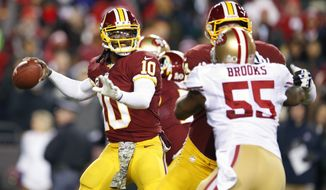 Washington Redskins quarterback Robert Griffin III prepares to pass the ball as San Francisco 49ers outside linebacker Ahmad Brooks closes in during the first half of an NFL football game in Landover, Md., Monday, Nov. 25, 2013. (AP Photo/Evan Vucci)