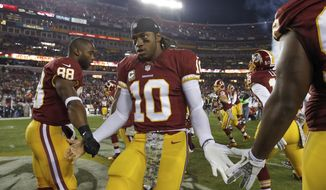 Washington Redskins quarterback Robert Griffin III greets his teammates as he runs on the field before the first half of an NFL football game against the San Francisco 49ers in Landover, Md., Monday, Nov. 25, 2013. (AP Photo/Alex Brandon)