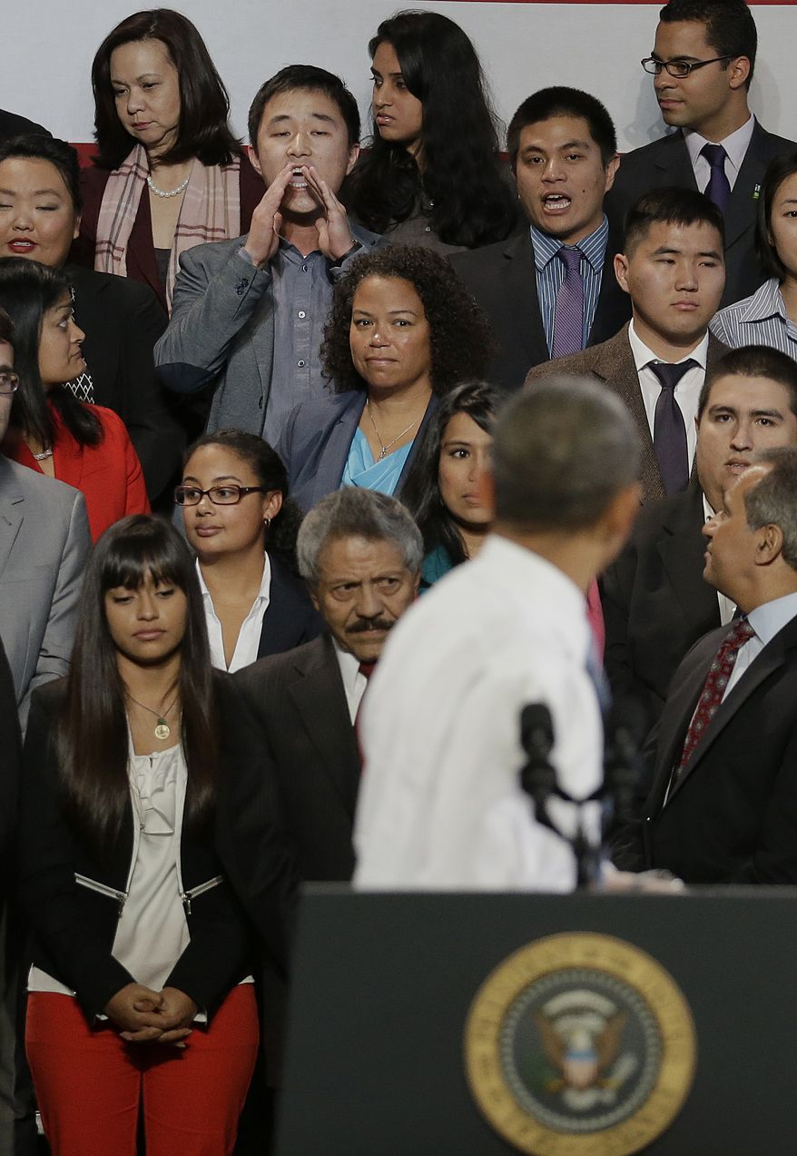 Ju Hong, third from top left, interrupts President Barack Obama's speech about immigration reform, Monday, Nov, 25, 2103, at the Betty Ann Ong Chinese Recreation Center in San Francisco. (AP Photo/Jeff Chiu)