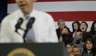 """President Barack Obama, left, has his speech interrupted by Ju Hong, right on stage, who heckled him about anti-deportation policies, Monday, Nov. 25, 2013, at the Betty Ann Ong Chinese Recreation Center in San Francisco. The young man shouted about his family being separated for Thanksgiving, and said Obama should use his executive power to stop this. """"Stop deportations, yes we can,"""" the man and other people chanted. The Obama stopped Secret Service agents who tried to remove the protesters. (AP Photo/Pablo Martinez Monsivais)"""