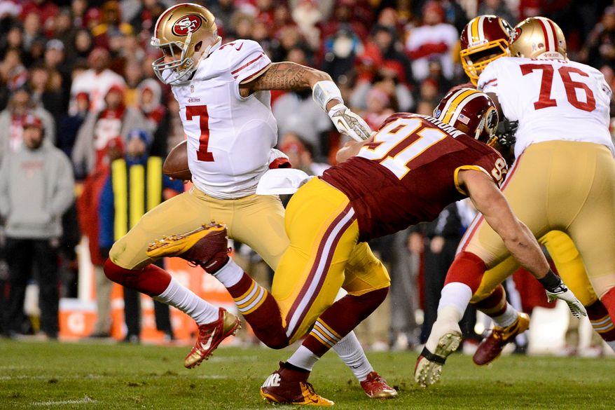San Francisco 49ers quarterback Colin Kaepernick (7), left, scrambles away from Washington Redskins outside linebacker Ryan Kerrigan (91) before he is sacked in the first quarter as the Washington Redskins play the San Francisco 49ers in Monday Night Football at FedExField, Landover, Md., Monday, November 25, 2013. (Andrew Harnik/The Washington Times)