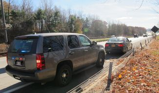 An unmarked New York State Police SUV is seen in Mount Pleasant, N.Y., on Thursday, Nov. 14, 2013, after a trooper pulled over another driver for distracted driving. Troopers are using a fleet of the tall SUVs as part of a crackdown on texting while driving. (AP Photo/Jim Fitzgerald)