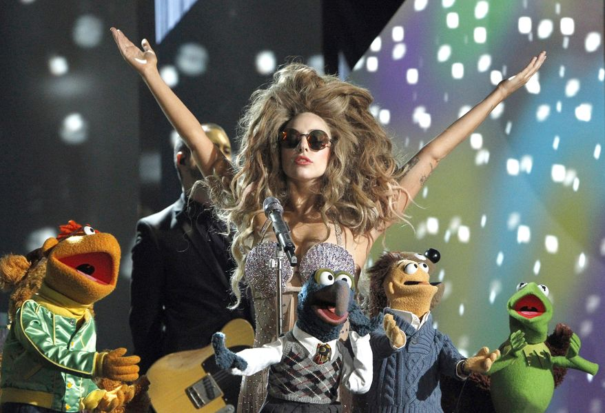 """This image released by ABC shows performer Lady Gaga, center, with muppet characters, including Kermit the Frog, right, and Gonzo, foreground center, in a promotional photo from the upcoming show """"Lady Gaga & The Muppets' Holiday Spectacular,"""" airing Thursday, Nov. 28  at 9:30 EST on ABC. (AP Photo/ABC, Rick Rowell)"""