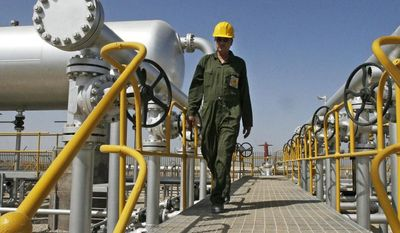 ** FILE ** Iranian oil technician Majid Afshari makes his way to the oil separator facilities in Iran's Azadegan oil field southwest of Tehran on April 15, 2008. (Associated Press)