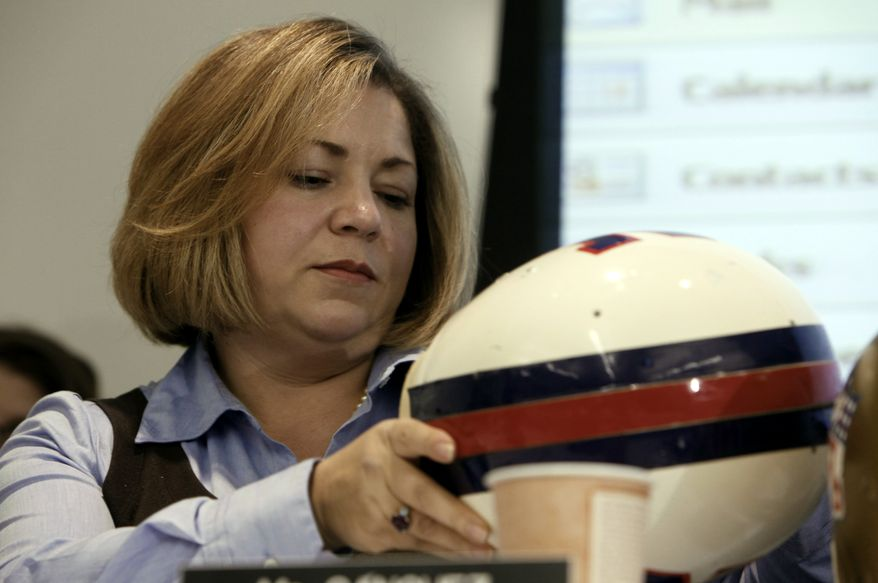 """Rep. Linda Sanchez, D-Calif., views a older NFL football helmet during a hearing titled """"Legal Issues Relating to Football Head Injuries, Part II"""" in Detroit, Monday, Jan. 4, 2010. (AP Photo/Paul Sancya) ** FILE **"""