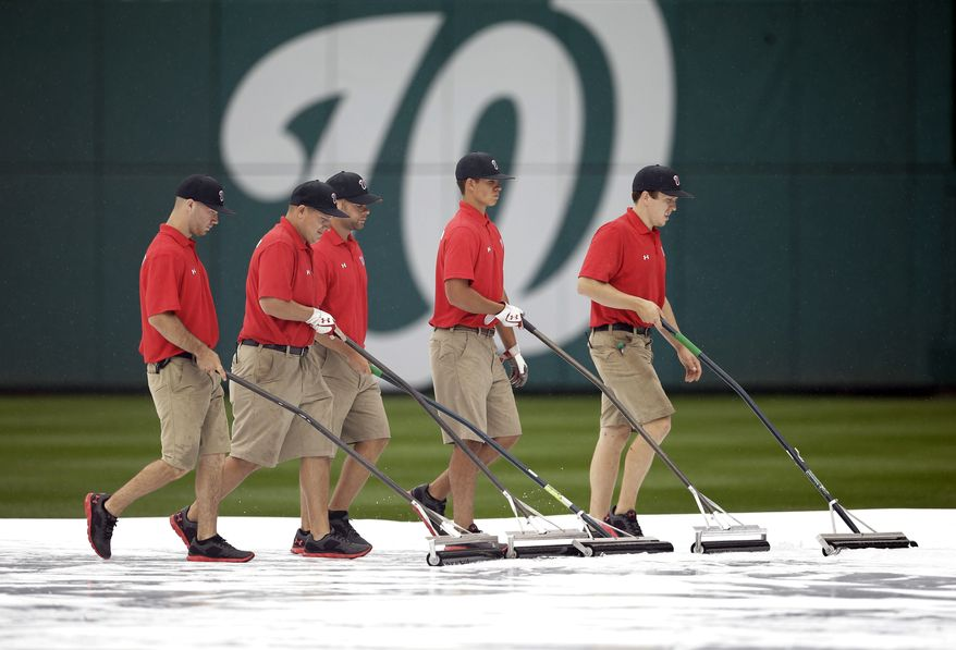 Members of the grounds crew squeegee water off the infield tarp during a rain delay before a baseball game between the Washington Nationals and Arizona Diamondbacks at Nationals Park, Thursday, June 27, 2013, in Washington.(AP Photo/Pablo Martinez Monsivais)