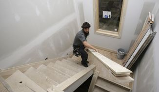 ** FILE ** In this Monday, Nov. 11, 2013, photo, Will Hostetler, a carpenter with Larry Block Builders, carries trim downstairs at a new home under construction, in Pepper Pike, Ohio. (AP Photo/Tony Dejak)