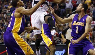 Washington Wizards guard John Wall (2) shoots between Los Angeles Lakers guards Wesley Johnson (11) and Jordan Farmar (1) in the second half of an NBA basketball game Tuesday, Nov. 26, 2013, in Washington. Wall had 31 points, and the Wizards won 116-111. (AP Photo/Alex Brandon)