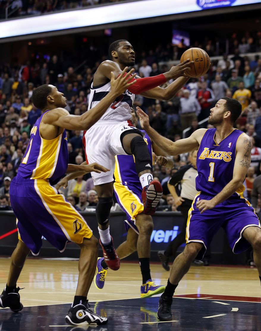 Washington Wizards guard John Wall (2) shoots between Los Angeles Lakers guards Wesley Johnson (11) and Jordan Farmar (1) in the second half of an NBA basketball game Tuesday, Nov. 26, 2013, in Washington. Wall had 31 points, and the Wizards won 116-111. (AP Photo/Alex Brandon)