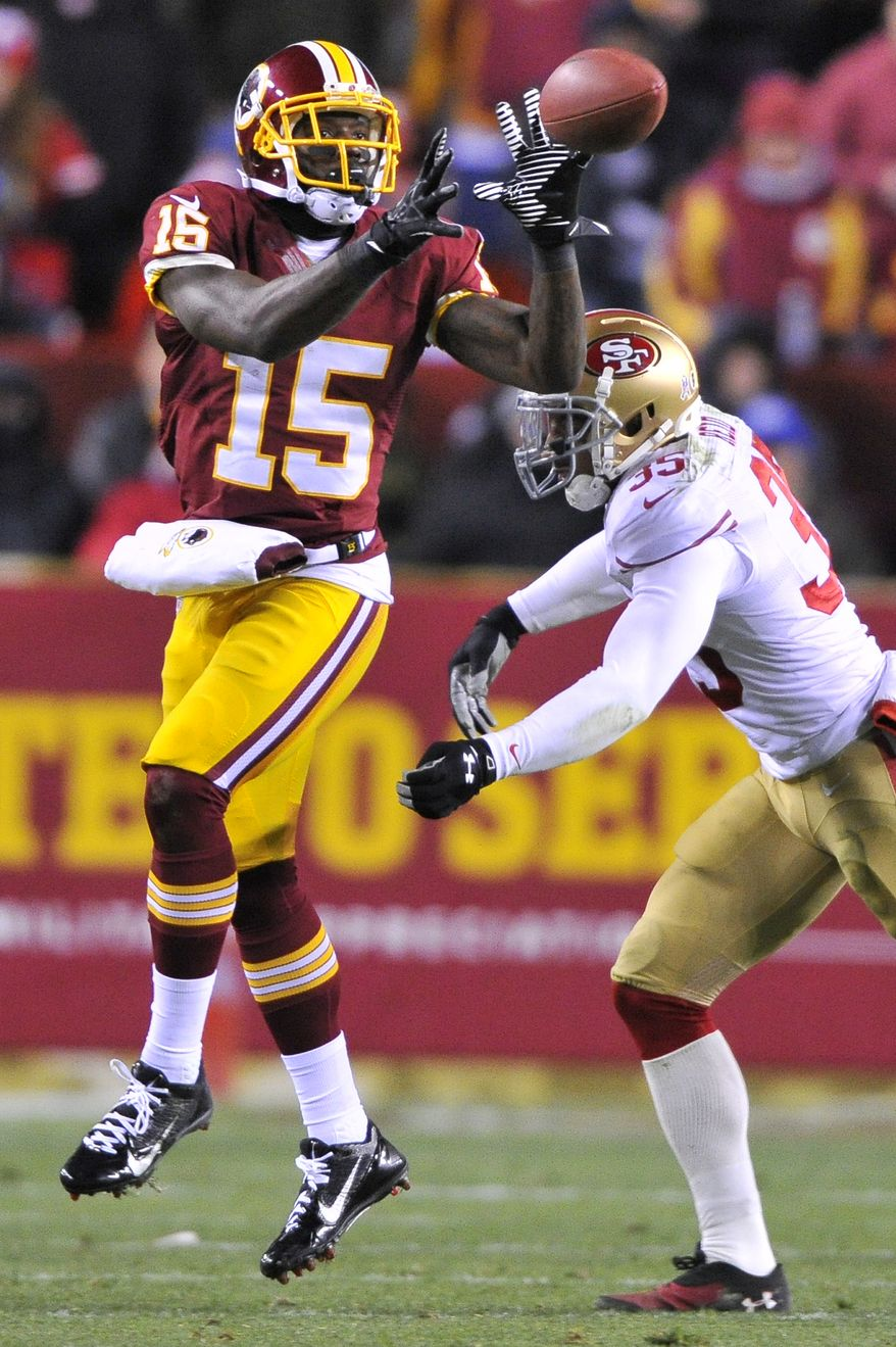 Washington Redskins wide receiver Josh Morgan (15) looks to haul in a pass against San Francisco 49ers free safety Eric Reid (35) at FedExField, Landover, Md., Novermber 25, 2013. (Preston Keres/Special for The Washington Times)