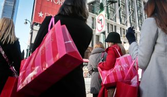 Shoppers carry Victoria Secret bags while crossing an intersection in Herald Square on Saturday. Despite signs that the economy is improving, big store chains like Wal-Mart and Kohl's don't expect Americans to have much holiday shopping cheer unless they see bold, red signs that offer huge discounts. (ASSOCIATED PRESS)