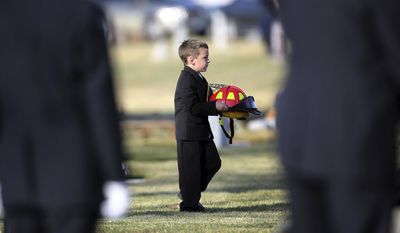 Five-year-old Jack Erickson, son of Eagle Fire Department Capt. Brandon Erickson, carries his father's helmet to his funeral at Meridian Cemetery on Tuesday, Nov. 26, 2013, in Meridian, Idaho. Erickson, 36, died at home Thursday following back surgery on Wednesday. (AP Photo/The Idaho Statesman, Kyle Green) MANDATORY CREDIT