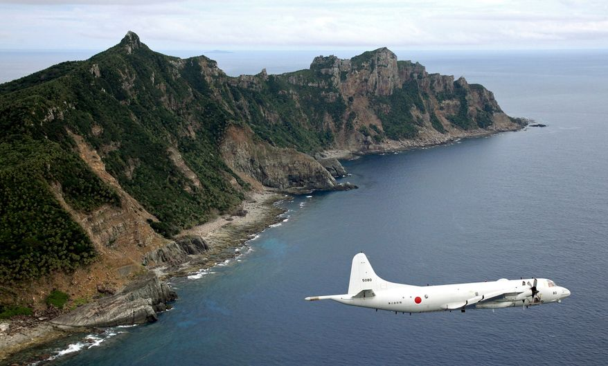 FILE - In this Thursday, Oct. 13, 2011 file photo, Japan Maritime Self-Defense Force's P-3C Orion surveillance plane flies over the disputed islands in the East China Sea, called the Senkaku in Japan and Diaoyu in China. China said Wednesday, Nov. 27, 2013 it had monitored two unarmed U.S. bombers that flew over the East China Sea in defiance of Beijing's declaration it was exercising greater military control over the area. Tuesday's flight of the B-52 bombers underscored U.S. assertions that it will not comply with Chinese demands that aircraft flying through its newly declared maritime air defense zone identify themselves and accept Chinese instructions. (AP Photo/Kyodo News, File)  JAPAN OUT