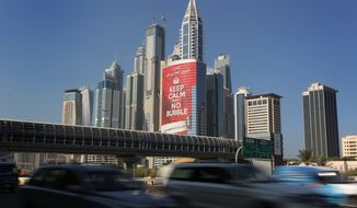 Cars whiz past the Marina District of Dubai, United Arab Emirates, on Wednesday, Nov. 13, 2013. (AP Photo/Kamran Jebreili)