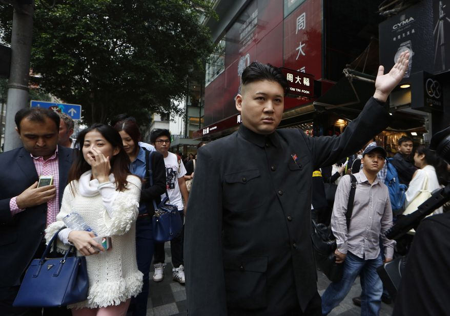 An impersonator of Kim Jong Un supreme leader of North Korea, who identified himself only as Howard, poses for the media in Hong Kong Wednesday Nov. 27, 2013.  The Hong Kong-born Australian musician, Howard refused to give his surname to keep his music career and his double act separate, claimed to be the world's first professional Kim Jong Un impersonator. (AP Photo/Kin Cheung)