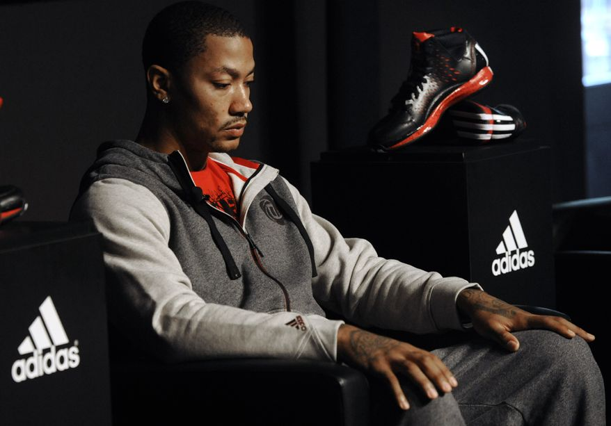 """FILE - In this Sept. 13, 2012 file photo, Chicago Bulls player Derrick Rose looks on during a press conference while unveiling his new shoe the Adidas D Rose 3 in Chicago. With Rose out for the season, industry experts say Adidas may need to rethink its NBA marketing campaign centered on the Chicago Bulls star. An Adidas spokeswoman says the sports apparel giant's plans remain unchanged """"at this time"""" and will be updated as needed. (AP Photo/Paul Beaty, File)"""