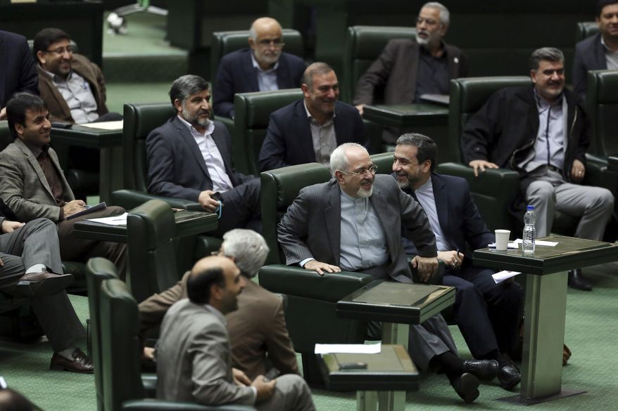 Iranian Foreign Minister Mohammad Javad Zarif, center, shares a light moment with members of the parliament as he arrives there in Tehran, Iran, Wednesday, Nov. 27, 2013. Hard-line Iranian politicians publicly criticized the deal reached in Geneva last week over the Islamic Republic's nuclear program, an agreement that has largely been welcomed by Iranians. (AP Photo/Ebrahim Noroozi)