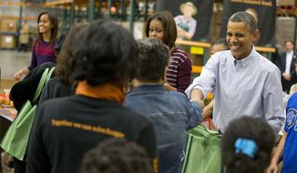 President Barack Obama smiles as he participates in a Thanksgiving service project by handing out food at the Capital Area Food Bank on Wednesday, Nov. 27, 2013 in Washington. The Capital Area Food Bank distributes 30 million pounds of food annually. (AP Photo/Evan Vucci)