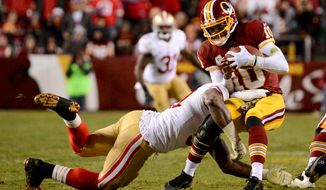 Washington Redskins quarterback Robert Griffin III (10) is sacked by San Francisco 49ers tight end Demarcus Dobbs (83) in the fourth quarter as the Washington Redskins play the San Francisco 49ers in Monday Night Football at FedExField, Landover, Md., Tuesday, Nov. 26, 2013. (Andrew Harnik/The Washington Times)