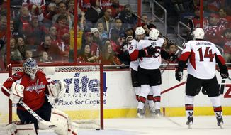 Ottawa Senators center Zack Smith (15) celebrates his goal with right wing Chris Neil (25) and left wing Colin Greening (14) as Washington Capitals goalie Braden Holtby (70) kneels in the net in the third period of an NHL hockey game, Wednesday, Nov. 27, 2013, in Washington. The Senators won 6-4. (AP Photo/Alex Brandon)