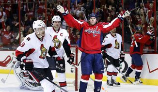 Washington Capitals center Brooks Laich (21) celebrates his goal as Ottawa Senators left wing Milan Michalek (9), from the Czech Republic, and center Jason Spezza (19) skate nearby in the first period of an NHL hockey game, Wednesday, Nov. 27, 2013, in Washington. (AP Photo/Alex Brandon)