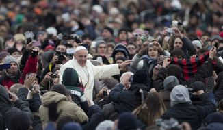 Pope Francis waves to faithful as he is driven through the crowd during his weekly general audience in St. Peter's Square at the Vatican, Wednesday, Nov. 27, 2013. Francis has cheered the thousands of pilgrims who braved a cold snap belting Italy to attend his audience, saying they were courageous to come out. Francis himself was bundled up in a white double-breasted winter coat and scarf, but it wasn't enough. He had to use his sleeves as a muffler to keep his hands warm amid temperatures that on Wednesday dipped to freezing with the wind chill factored in. (AP Photo/Alessandra Tarantino)