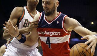 Washington Wizards' Marcin Gortat (4) tries to drive past Milwaukee Bucks' John Henson during the first half of an NBA basketball game Wednesday, Nov. 27, 2013, in Milwaukee. (AP Photo/Morry Gash)