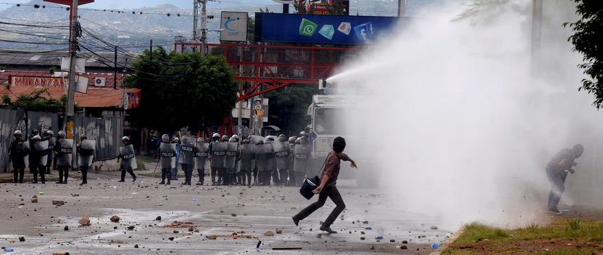A man throws a stone at riot police spraying a water cannon during clashes in Tegucigalpa, Honduras. (Associated Press photograhs)