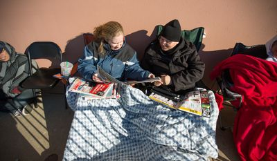 Bill and Lisa Carter, of Lorton, VA., look at Black Friday advertisements from underneath the warmth of a large blanket, as they wait outside of Best Buy hours in advance of the 6pm opening, in hopes to catch a great Black Friday deal, in Springfield, VA., Thursday, November 27, 2013.  (Andrew S Geraci/The Washington Times)