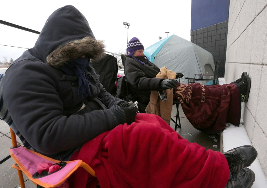 David Thao and Brenda O'Keefe are all bundled up as they are among the first in line to get into a Best Buy store in Wausau, Wis., Thursday, Nov. 28, 2013. There were two groups of people ahead of them who had pitched tents as they awaited the 6 p.m. Thanksgiving Day opening of the store. (AP Photo/Daily Herald Media, Dan Young)