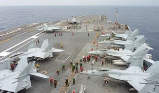 U.S. Navy FA-18 Hornets cram the flight deck of the USS George Washington during a joint military exercise with Japan in the Pacific Ocean near Japan's southernmost island of Okinawa on Nov. 28, 2013. (AP Photo/Kyodo News)