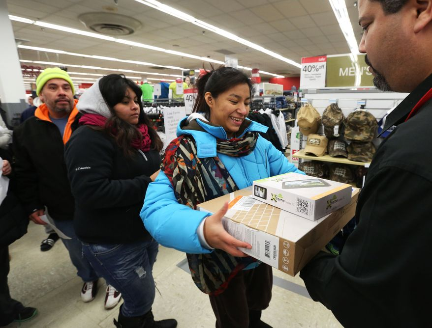 IMAGE DISTRIBUTED FOR KMART - Rosa Rodriguez, of Chicago, picks up a tablet and a laptop during the doorbuster deals at the Kmart store on Addison St., on Thursday, Nov. 28, 2013 in Chicago, Ill. Rodriguez arrived at 1:30am for the first deals of the season as Kmart was the first major retailer to open it's doors for pre-Black Friday shopping on Thanksgiving Day at 6am. (John Konstantaras/AP Images for Kmart)