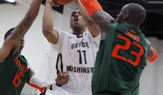 George Washington's Kethan Savage (11) splits between Miami guard Rion Brown (15) and center Tonye Jekiri (23) in the first half of an NCAA college basketball game at the Wooden Legacy tournament, Thursday, Nov. 28, 2013, in Fullerton, Calif. (AP Photo/Alex Gallardo)