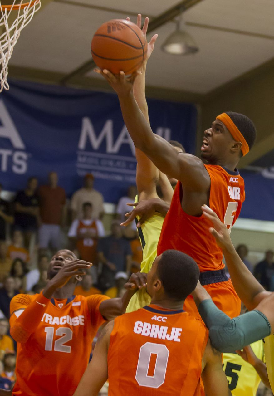 Syracuse forward C.J. Fair (5) shoots a layup as his teammates center Baye Moussa Keita (12) and forward Michael Gbinije (0) watch during the second half of an NCAA college basketball game at the Maui Invitational on Wednesday, Nov. 27, 2013, in Lahaina, Hawaii. Syracuse won 74-67 to win the tournament. (AP Photo/Eugene Tanner)