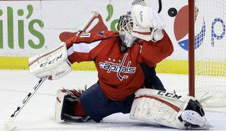Washington Capitals goalie Braden Holtby deflects a puck as he defends the goal during the second period of an NHL hockey game in Washington, Friday, Nov. 29, 2013. Washington Capitals won 3-2 in overtime. (AP Photo/Carolyn Kaster)