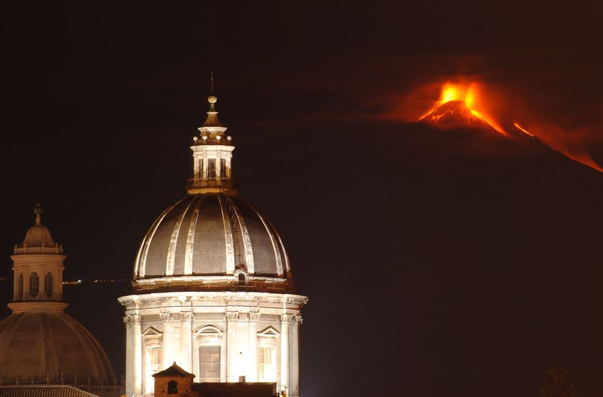 Mt. Etna is seen behind two cupolas as it spews lava during an eruption near the Sicilian town of Catania, Italy, late Thursday, Nov. 28, 2013. Etna's eruptions aren't infrequent, the last one occurred on Nov. 23.  (AP Photo/Salvatore Allegra)