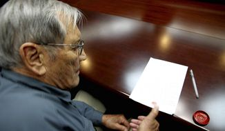 In this Nov. 9, 2013 photo released by the Korean Central News Agency (KCNA) and distributed Nov. 30, 2013 by the Korea News Service,  U.S. citizen Merrill Newman, 85, applies his thumb print to a document which North Korean authorities say was an apology which Newman wrote and read in North Korea. Newman, an avid traveler and retired finance executive, was taken off a plane Oct. 26 by North Korean authorities while preparing to leave the country after a 10-day tour. (AP Photo/KCNA via KNS) JAPAN OUT UNTIL 14 DAYS AFTER THE DAY OF TRANSMISSION