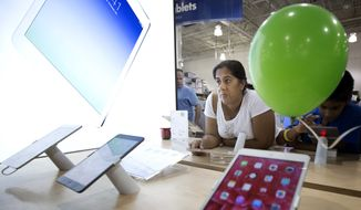 Shamela Paul shops for an iPad at the Pembroke Pines, Fla. Best Buy store, Friday, Nov. 29, 2013. Black Friday, the day after Thanksgiving, is the nation's biggest shopping day of the year.  (AP Photo/J Pat Carter)