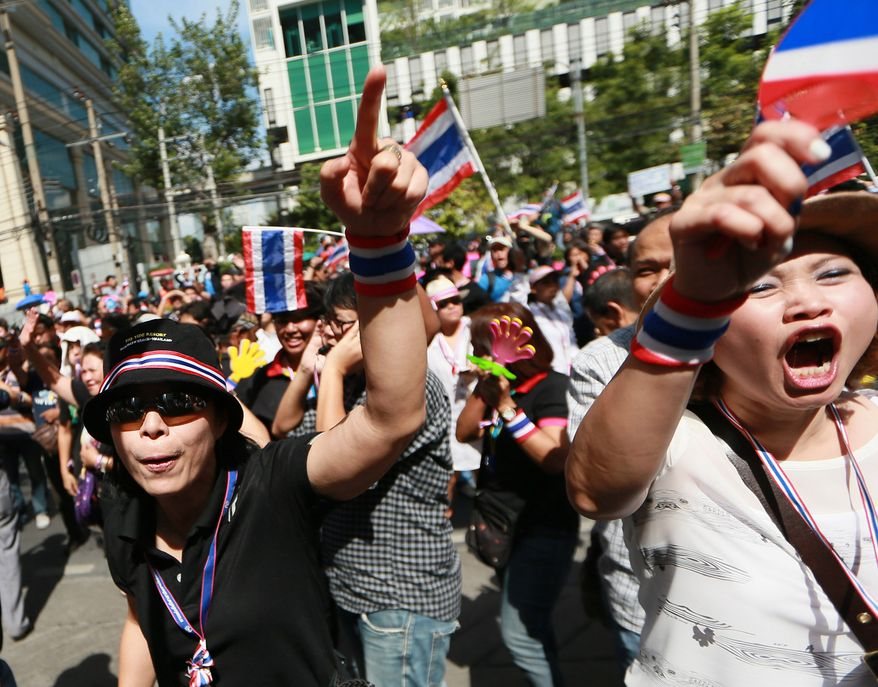 Anti-government protesters shout slogans outside the headquarters of Prime Minister Yingluck Shinawatra's ruling Pheu Thai Party in Bangkok, Thailand, Friday, Nov. 29, 2013. The protesters staged a rally in a bid to topple Yingluck outside the party headquarters where hundreds of riot police stood guard to prevent them from entering. (AP Photo/Wason Wanichakorn)