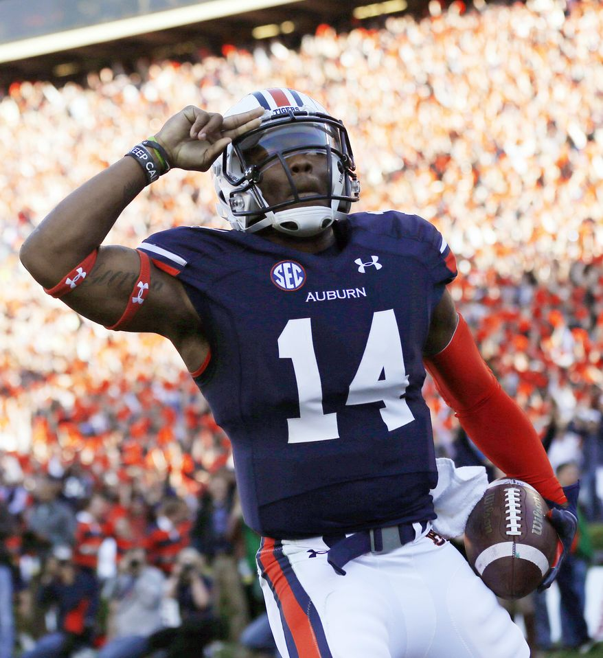 Auburn quarterback Nick Marshall (14) salutes after scoring against Alabama on a 45-yard touchdown run in the first half of an NCAA college football game in Auburn, Ala., Saturday, Nov. 30, 2013. (AP Photo/Dave Martin)