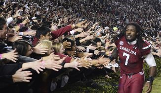 South Carolina defensive end Jadeveon Clowney (7) celebrates with fans after defeating Clemson 31-17 in an NCAA college football game on Saturday, Nov. 30, 2013, in Columbia, S.C. (AP Photo/Richard Shiro)