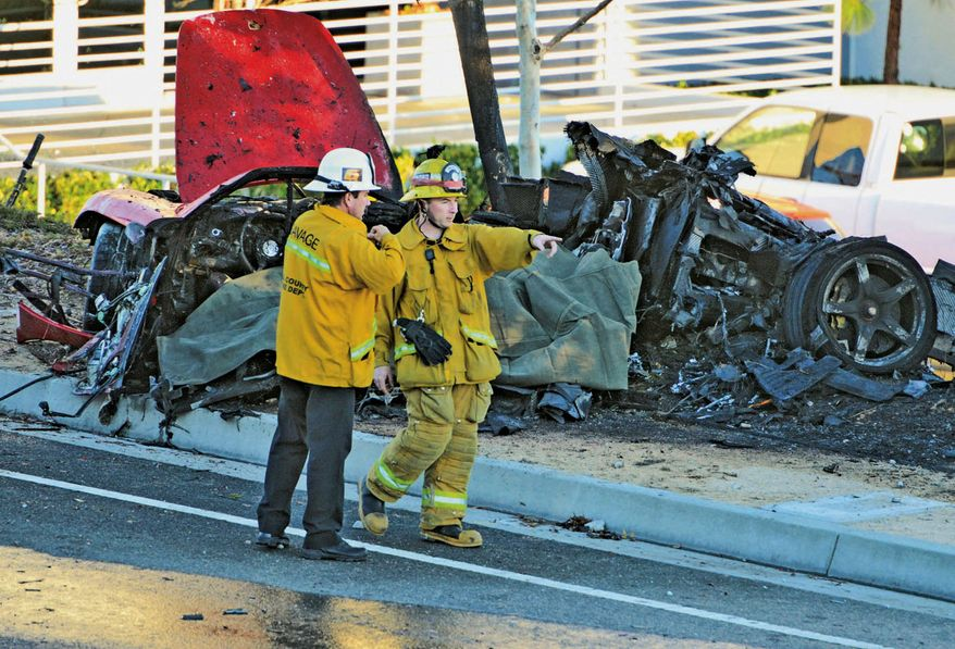 """Sheriff's deputies work near the wreckage of a Porsche that crashed into a light pole on Hercules Street near Kelly Johnson Parkway in Valencia, Calif., on Saturday, Nov. 30, 2013. A publicist for actor Paul Walker says the star of the """"Fast & Furious"""" movie series died in the crash north of Los Angeles. He was 40. Ame Van Iden says Walker died Saturday afternoon. No further details were released. (AP Photo/The Santa Clarita Valley Signal, Dan Watson)"""