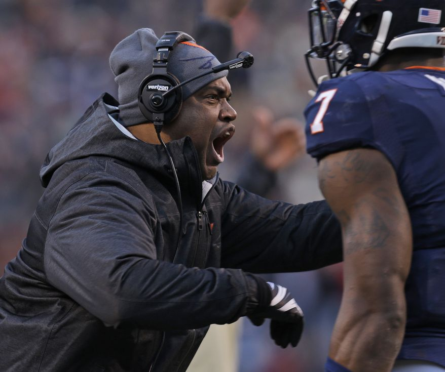 Virginia head coach Mike London reacts to a call during the first half of an NCAA college football game against Virginia Tech in Charlottesville, Va., Saturday, Nov. 30, 2013. (AP Photo/Steve Helber)