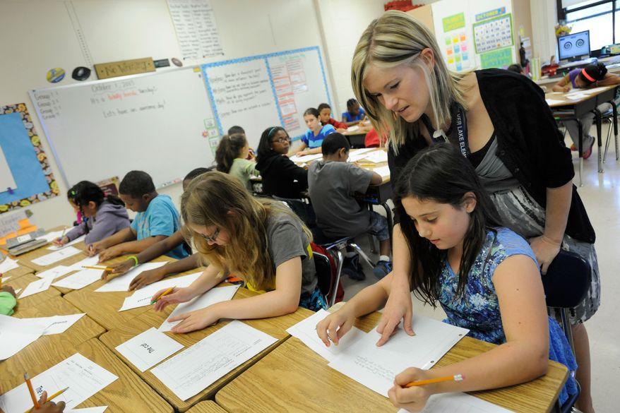 **FILE** A fifth-grade teacher helps students at Silver Lake Elementary School in Middletown, Del. (AP Photo/Steve Ruark)