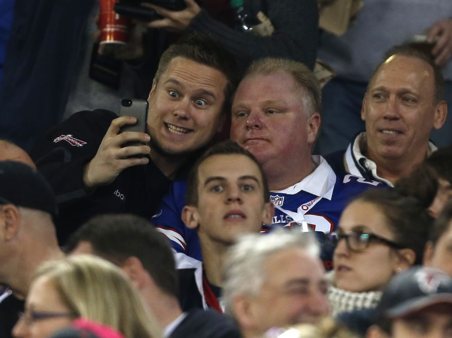 Toronto Mayor Rob Ford, right, poses with a fan during the first half of an NFL football game between the Atlanta Falcons and the Buffalo Bills on Sunday, Dec. 1, 2013, in Toronto. (AP Photo/Gary Wiepert)