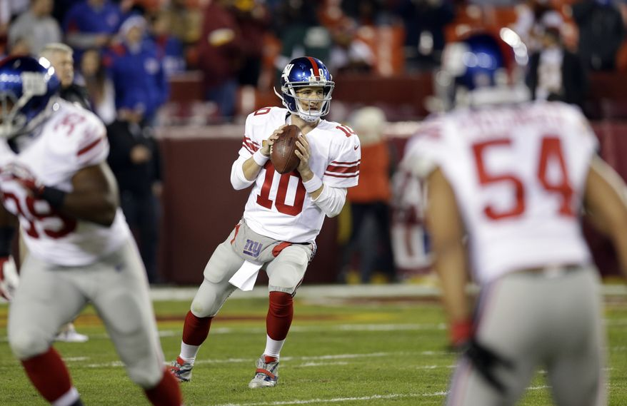 New York Giants quarterback Eli Manning (10) warms up before an NFL football game against the Washington Redskins, Sunday, Dec. 1, 2013, in Landover, Md. (AP Photo/Patrick Semansky)