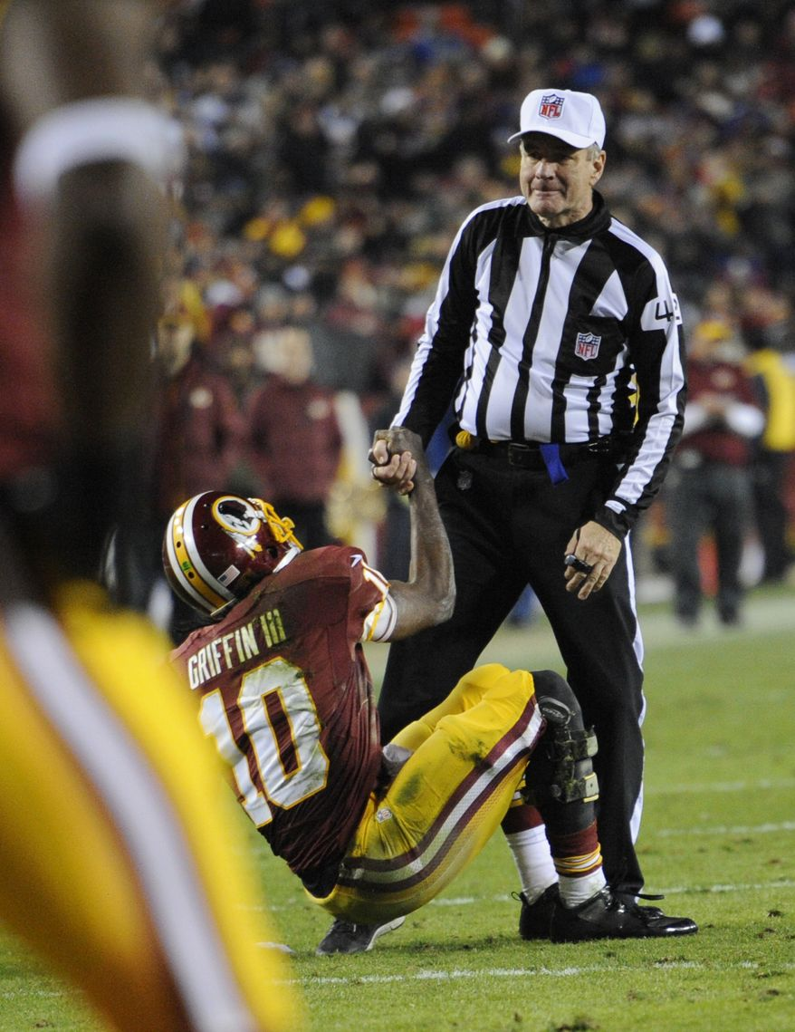 Washington Redskins quarterback Robert Griffin III (10) is helped up by referee Jeff Triplette during the second half of an NFL football game against the New York Giants Sunday, Dec. 1, 2013, in Landover, Md. (AP Photo/Nick Wass)