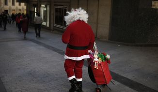 A man dressed as Santa Claus walks around the streets of central Madrid and charges for photographs taken with him on Sunday, Dec. 1, 2013. (AP Photo/Andres Kudacki)
