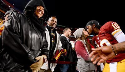 Parents of Washington Redskins quarterback Robert Griffin III (10) Jackie Griffin, left, and Robert Griffin Jr., second from left, watch as Griffin kisses his wife Rebecca Liddicoat, before the Washington Redskins play the New York Giants in Sunday Night Football at FedExField, Landover, Md., Sunday, December 1, 2013. (Andrew Harnik/The Washington Times)